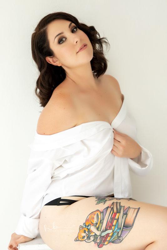 Women wearing white shirt with cat sitting on books tattooed on her leg